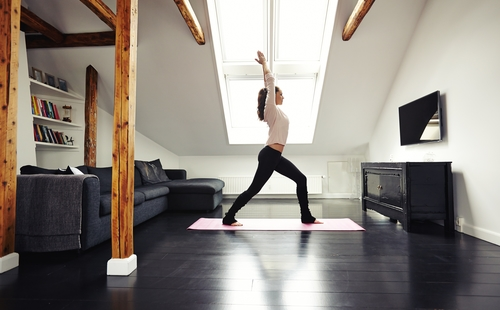 lady doing yoga workout at home. Fitness model exercising in living room.